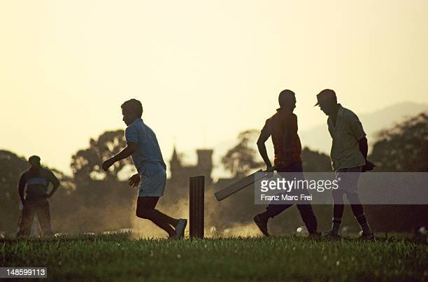 men playing cricket in queens park savannah. - port of spain stock pictures, royalty-free photos & images