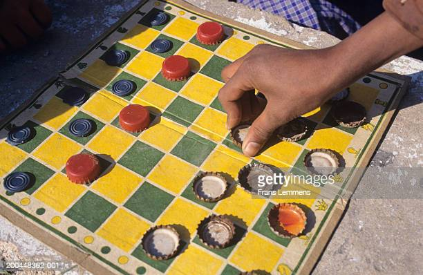Men playing draughts with bottle tops, close up, elevated view