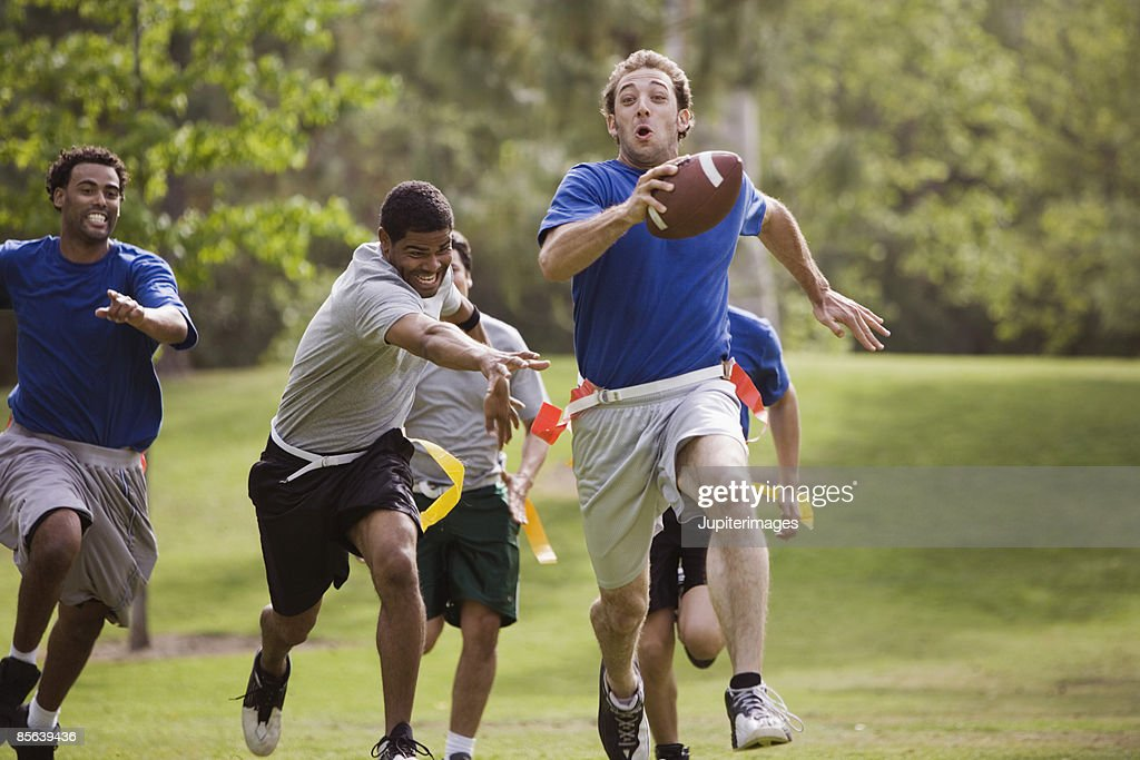 Men playing flag football together : Stock Photo