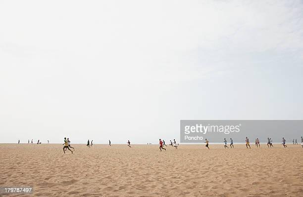 Men playing football at the beach