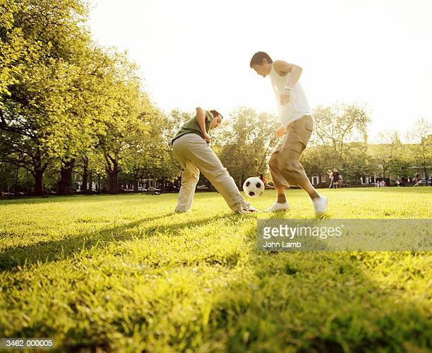 2 men playing football in park - football stock pictures, royalty-free photos & images