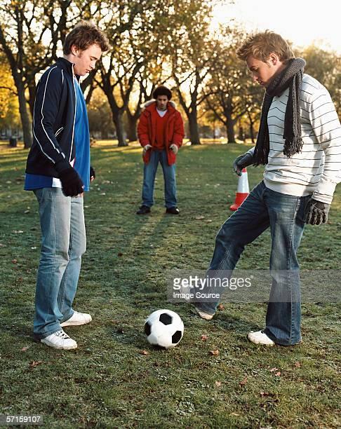 men playing football in park - passing sport - fotografias e filmes do acervo