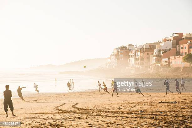 men playing football on the beach, taghazout, moro - agadir stock pictures, royalty-free photos & images