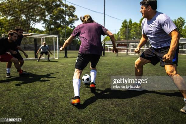mensen die vriendschappelijke gelijke op voetbalgebied spelen - sportevenement stockfoto's en -beelden