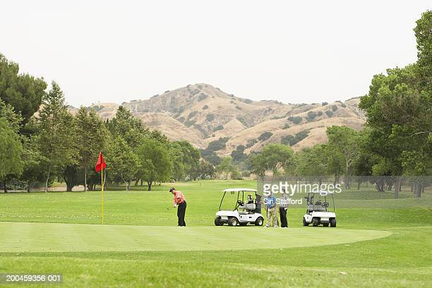Men playing golf, carts on green