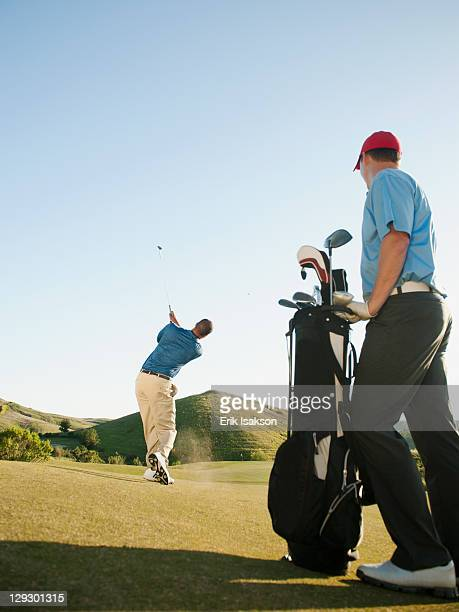 Men playing golf on golf course