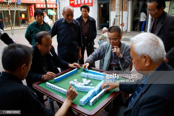 Men playing Mahjong board game for four players Xi'an China