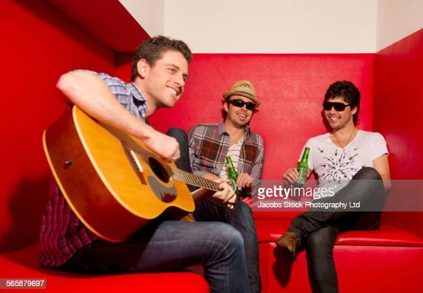 Men playing music and drinking in lounge