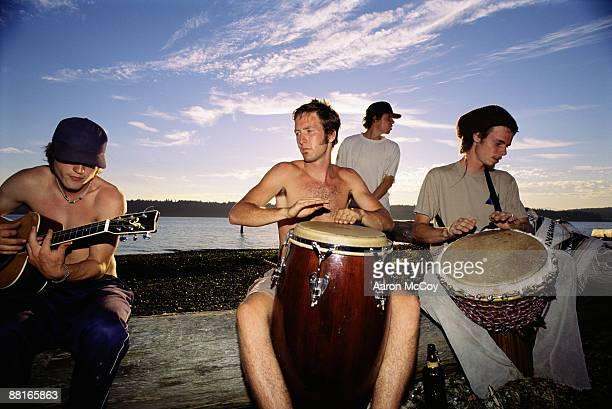 Men playing music by water at sunset