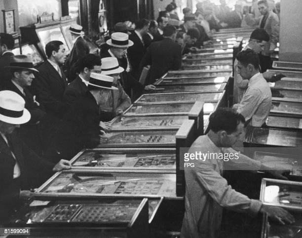 Men playing pinball machines in an amusement arcade USA circa 1935