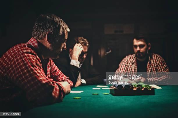 men playing poker game - gambling addiction stock pictures, royalty-free photos & images