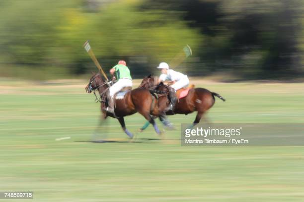 Men Playing Polo On Field