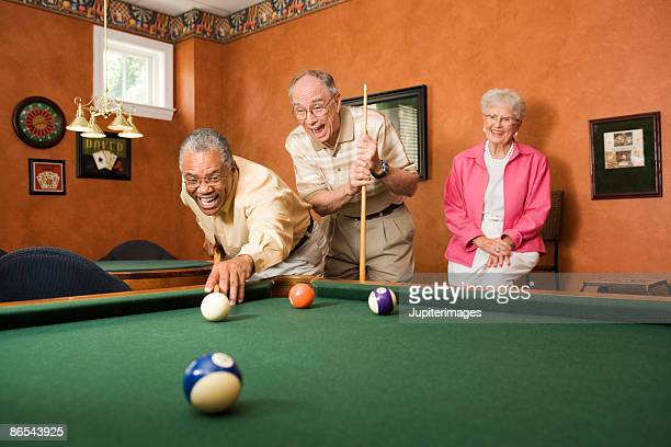 men playing pool as woman watches - old men playing pool stock pictures, royalty-free photos & images