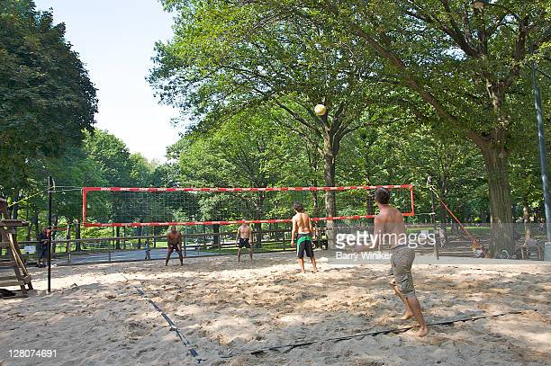 Men playing sand volleyball in Central Park, New York, NY