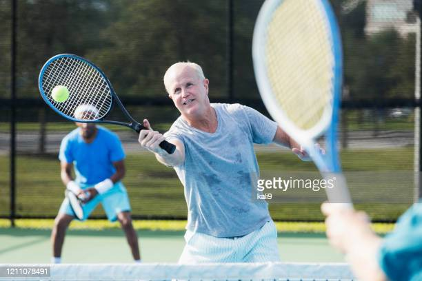 men playing tennis, hitting a volley - doubles sports competition format stock pictures, royalty-free photos & images