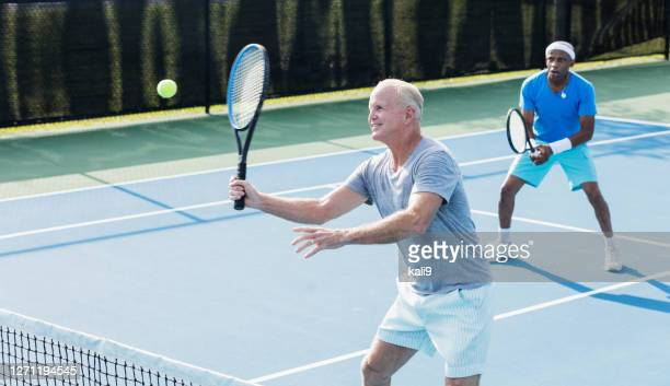 men playing tennis, hitting a volley - doubles stock pictures, royalty-free photos & images