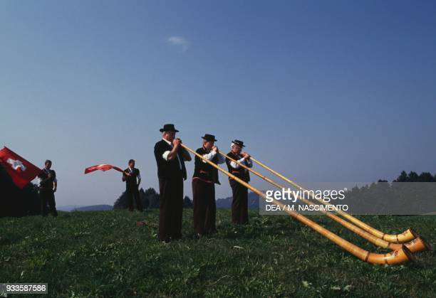 Men playing the alphorn during the Oberburg festival Canton of Bern Switzerland