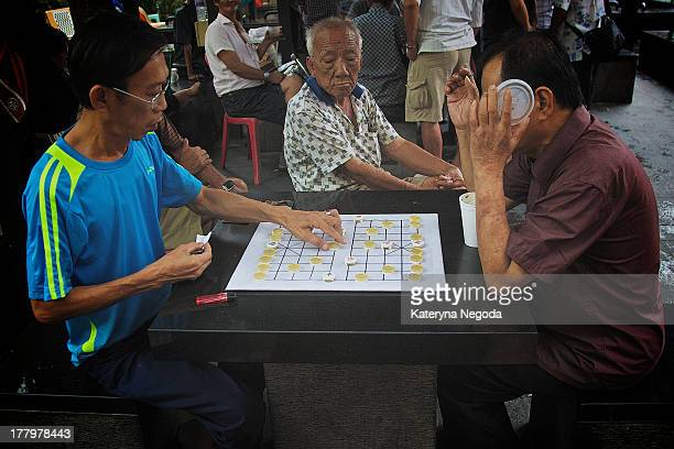 Men playing Xiangqi outside in China Town, Singapore. A xiangqi gameboard and pieces on the table.