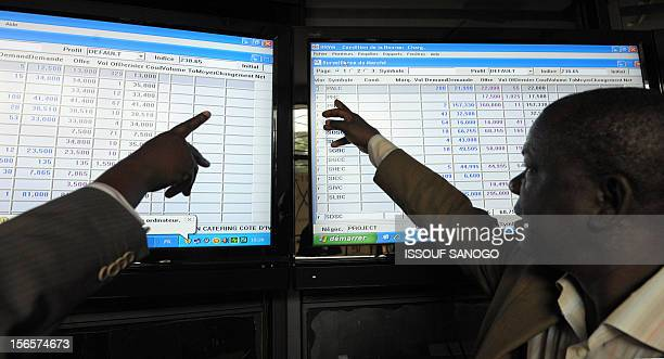 Men point at exchange rates posted on a board at the Regional Bourse for French West Africa where members of the West African Economic and Monetary...