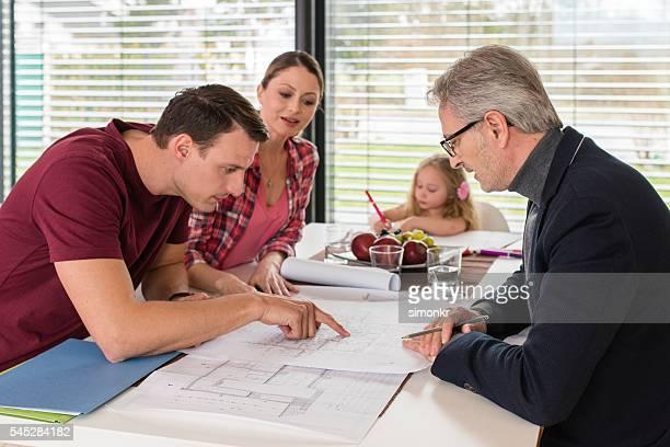 Men pointing blueprint
