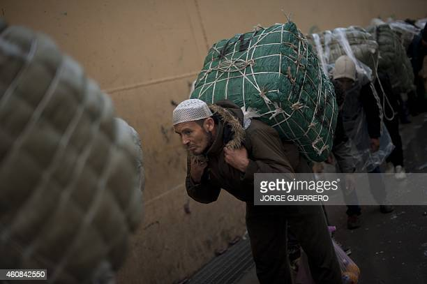 BAZINET Men porters carry bundles on their backs for transport across the El Tarajal boarder separating Morocco and Spain's North African enclave of...