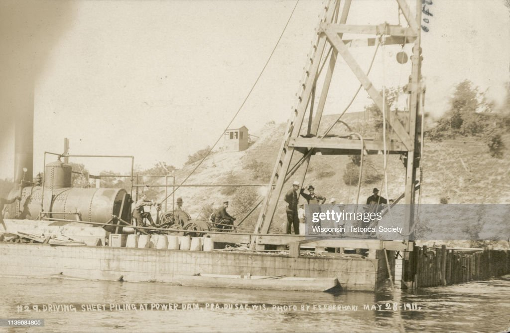 Men pose on a barge carrying a steam powered pile driver at
