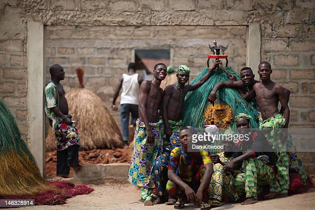 Men pose with a 'Zangbetto' ahead of a performance during a Voodoo ceremony on January 9 2012 in Ouidah Benin The Zangbetto are the 'Fons'...