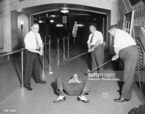 Men posing during a golf stunt, as they try to hit a golf ball off a man's nose while he is lying on his back on the floor in the lobby of the...