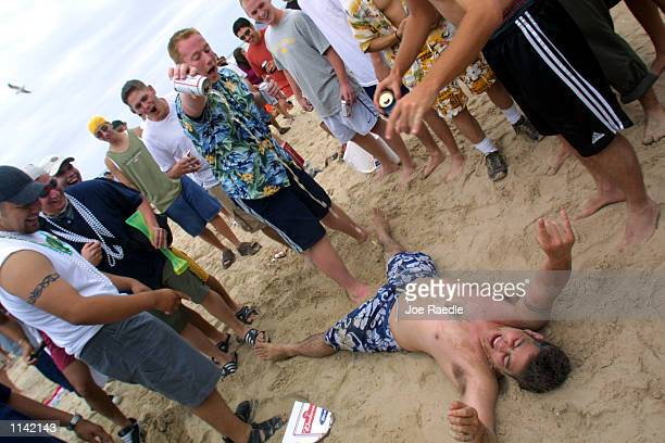 Men pour beer on a drunken student on the beach at South Padre Island Texas March 16 2001 during the annual rite of Spring Break Some 125000 revelers...