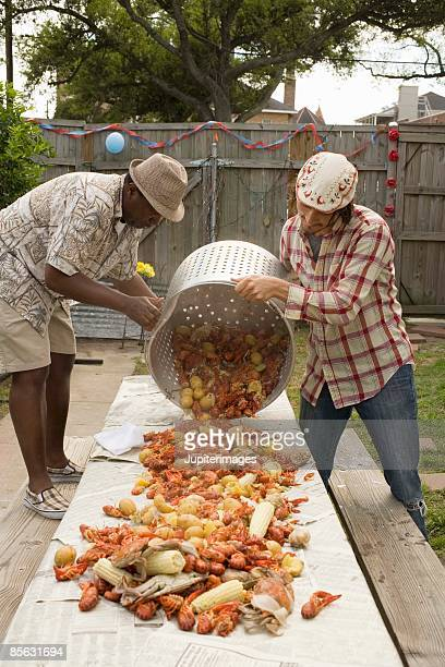 Men pouring seafood onto table