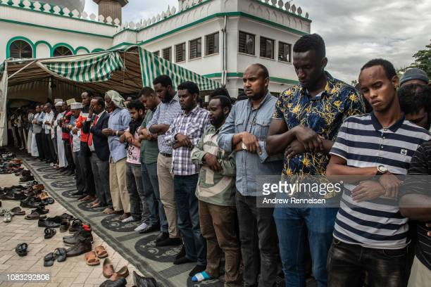 Men pray at a burial ceremony of Abdalla Mohamed Dahir and Feisal Ahmed on January 16 2018 in Nairobi Kenya The two men who worked together were...