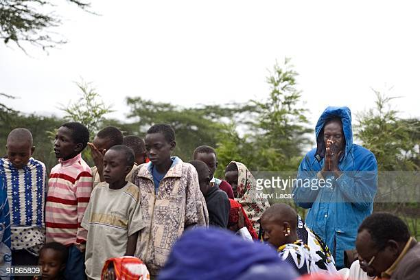 Men pray during a religious gathering December 29 2006 in the Maasai region of Kenya A counselor for the Tasaru Safehouse for Girls Lois Selena...