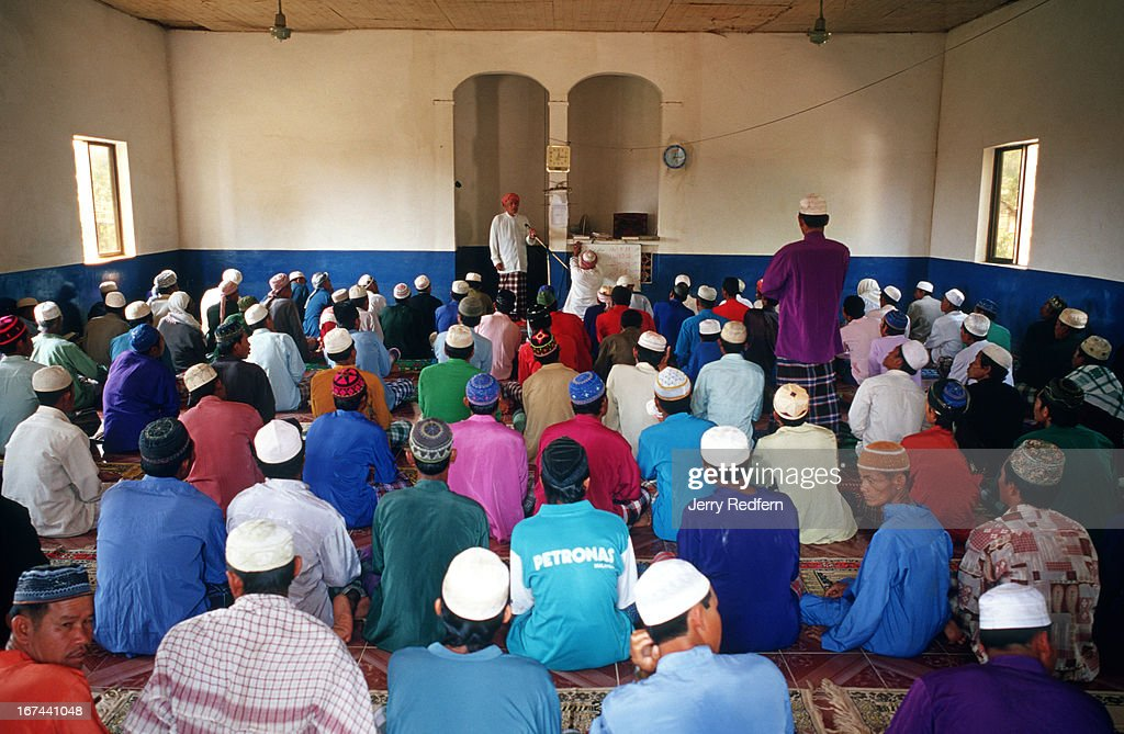 Men pray during Friday prayers at the Nour el Essan Mosque in Chong Koh village. The village consists of poor fishing families and a few farmers and traders..