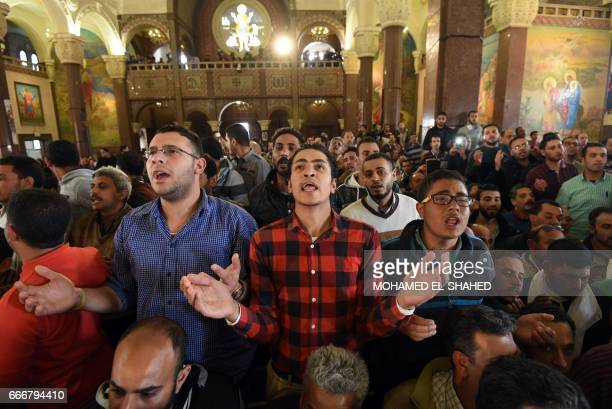 Men pray for the victims of the blast at the Coptic Christian Saint Mark's church in Alexandria the previous day during a funeral procession at the...