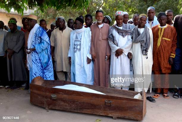 Men pray next to a coffin on January 7 2018 in a mosque in the regional capital Ziguinchor southern Senegal following an attack by armed men in the...