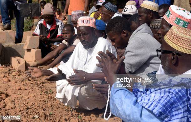 Men pray next to a grave in a cemetery in the regional capital Ziguinchor southern Senegal on January 7 2018 following an attack by armed men in the...