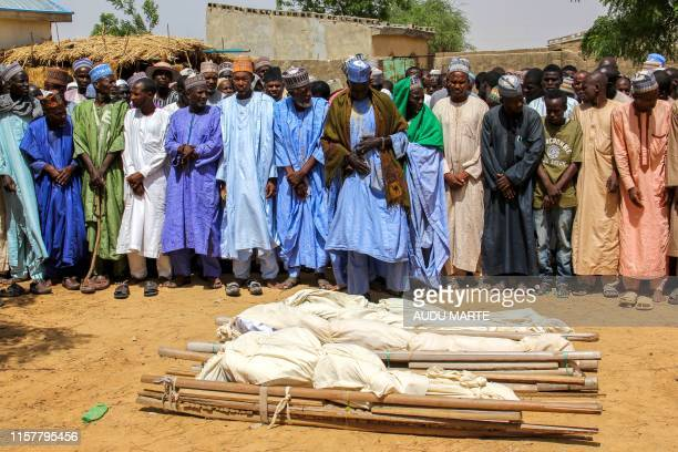 TOPSHOT Men pray next to coffins during a burial ceremony after two people were killed by Boko Haram fighters in Dalori camp for internally displaced...