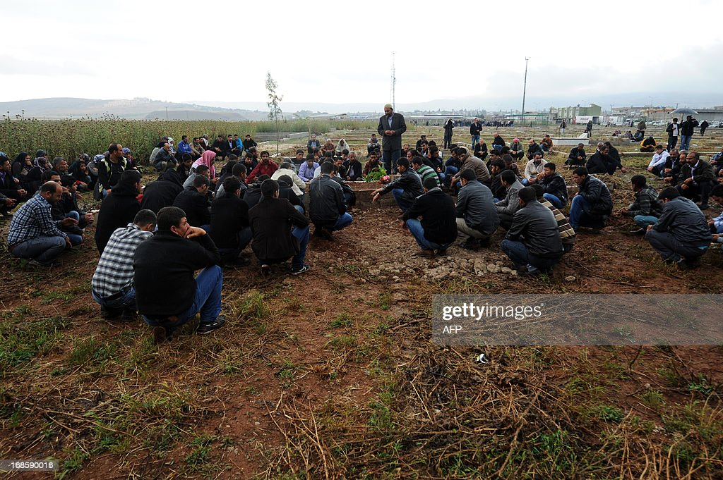 Men pray on May 12, 2013 at the graves of victims of a car bomb which went off on May 11 at Reyhanli in Hatay just a few kilometres from the main border crossing into Syria. Turkey was reeling from twin car bomb attacks which left at least 43 people dead in a town near the Syrian border, with Ankara blaming pro-Damascus groups and vowing to bring the perpetrators to justice. A Syrian minister denied on May 12 accusations that Damascus was behind a bomb attack in a Turkish town that left dozens dead, a day after Ankara blamed supporters of President Bashar al-Assad for the blasts.
