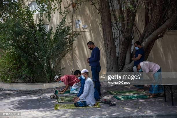 Men pray outside a mosque in the Deira neighborhood of Dubai on April 13, 2021 in Dubai, United Arab Emirates. Millions of muslims around the world...