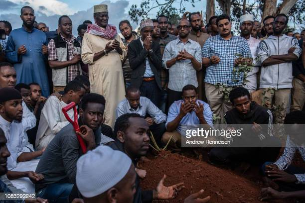 Men pray over the grave of Feisal Ahmed during a burial ceremony on January 16 2018 in Nairobi Kenya Ahmed and his colleague were killed after...