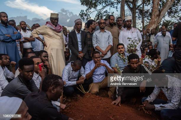 Men pray over the grave of Feisal Ahmed on January 16 2018 in Nairobi Kenya Ahmed and his colleague were killed after AlShabab militants stormed the...