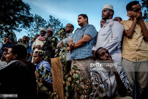 Men pray over the grave of Feisal Ahmed who was killed the previous day in an attack during his burial ceremony in Nairobi on January 16, 2018. - 21...