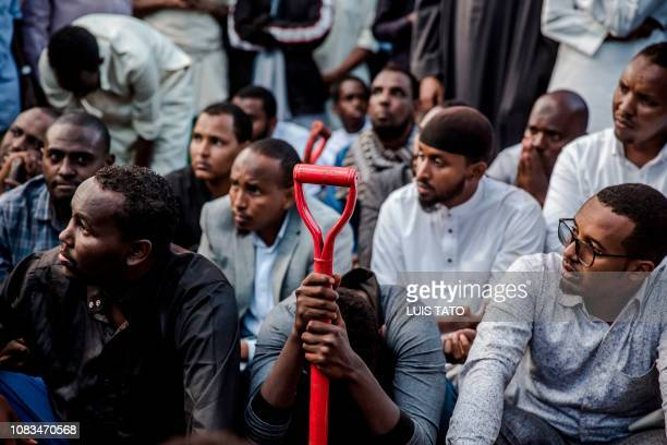 Men pray over the grave of Feisal Ahmed who was killed the previous day in an attack during his burial ceremony in Nairobi, on January 16, 2018. - 21...
