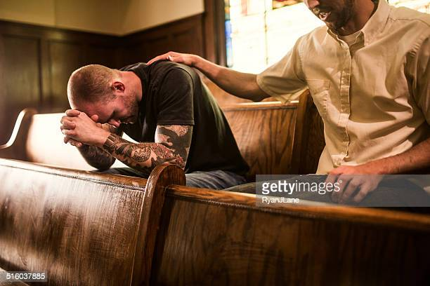 men pray together in church - priest stock pictures, royalty-free photos & images