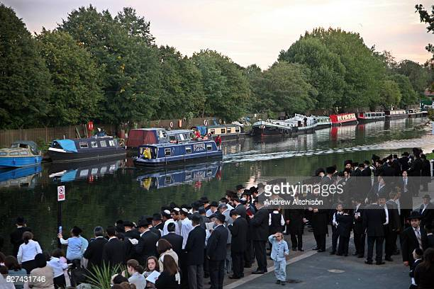 Men praying and casting away their sins into the river Lea Hackney London for Tashlich Tashlich is a Jewish practice that is performed during Rosh...