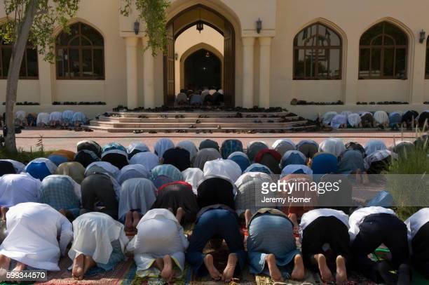 men praying outside abu dhabi mosque - gelovige stockfoto's en -beelden