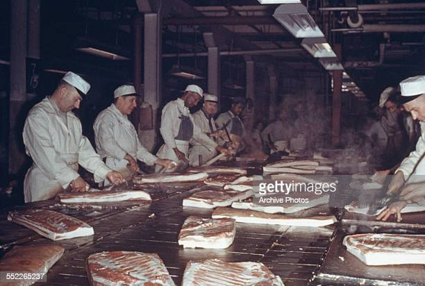Men prepare bacon at a meat packing plant in Chicago USA circa 1955