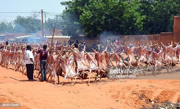Men prepare sheep carcases staked around a log fire along a street in Niamey as Muslims celebrate Eid alAdha on September 12 2016 Muslims across the...
