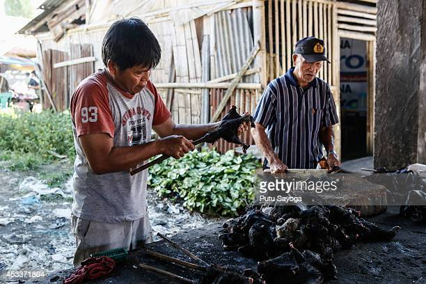 Men prepare to roast bats at Langowan traditional market on August 9 2014 in Langowan North Sulawesi The Langowan traditional market is famous for...