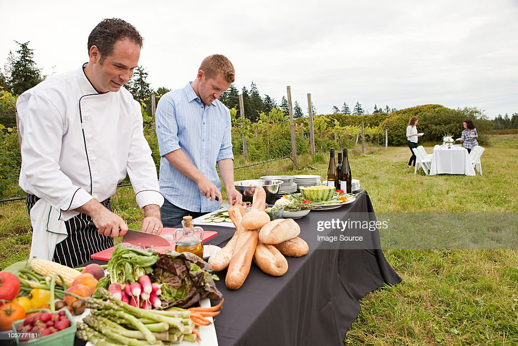 Men preparing food for dinner party in field : Stock Photo